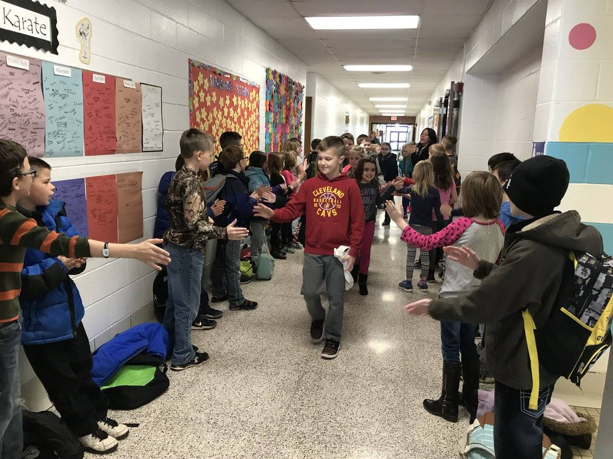 Students giving each other high fives in the hallway