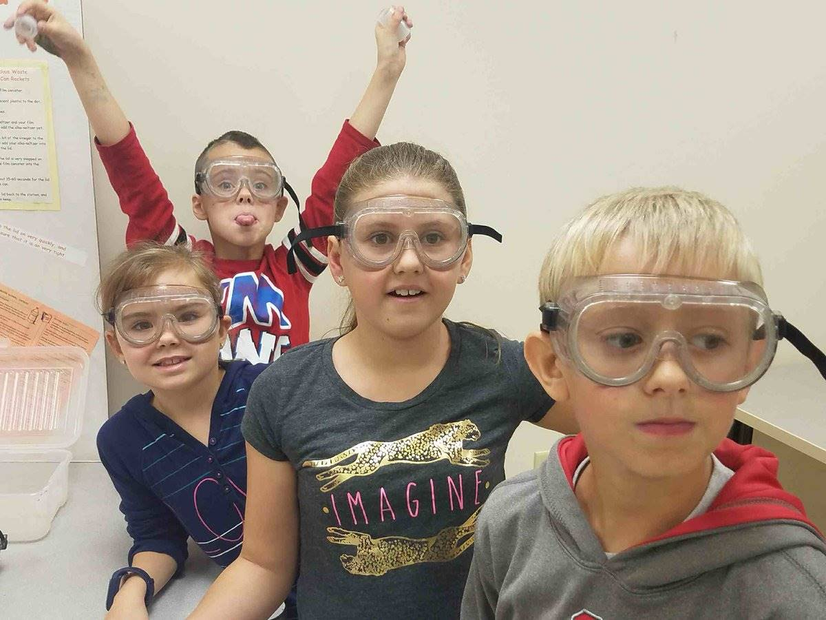 Students with goggles observe a science experiment