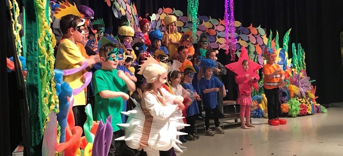 Students dressed up as sea creatures and singing for the spring music program