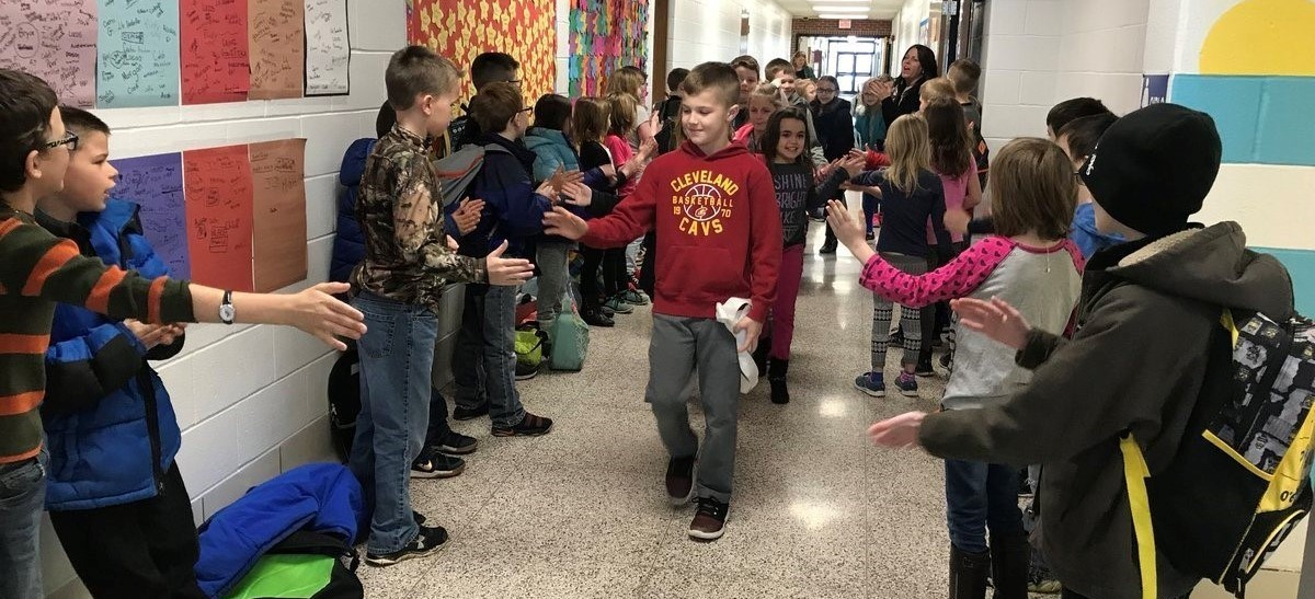 Students giving high fives to other students in the hallway