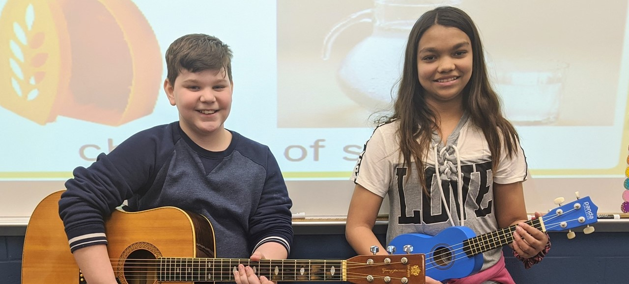 Two students holding guitars
