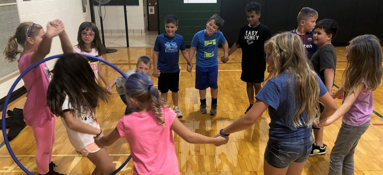 Students synergizing by transferring a hula hoop between them