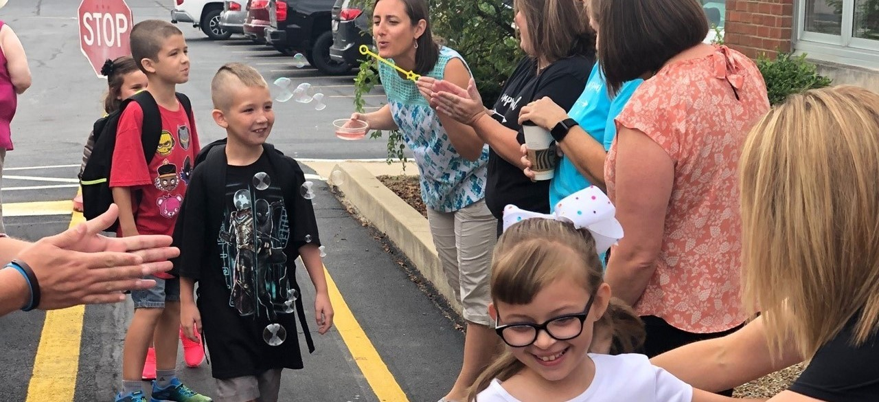 Welcoming students with bubbles and hugs