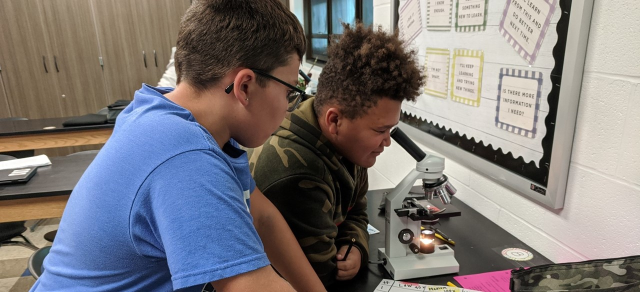 Students in Science class looking through microscopes